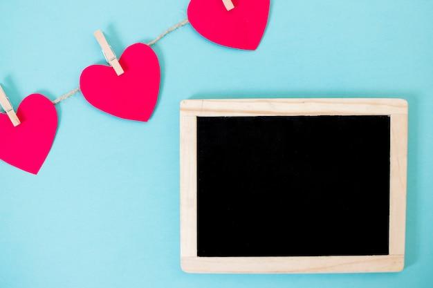 心の花輪を持つ小さな黒板