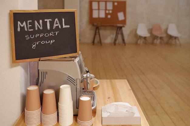 Маленькая доска с уведомлением о том, что группа психологической поддержки стоит на кофеварке с несколькими стопками бумажных стаканов рядом