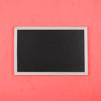 Small blank blackboard on coral painted wall