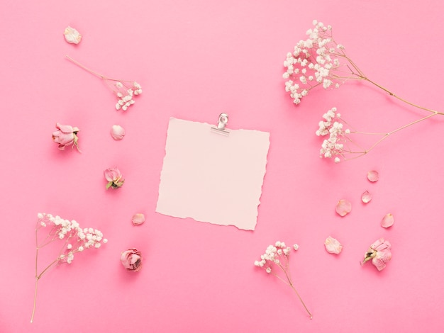 Small blank paper with flower branches on table