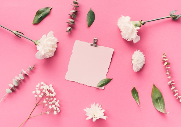 Small blank paper with flowers on table