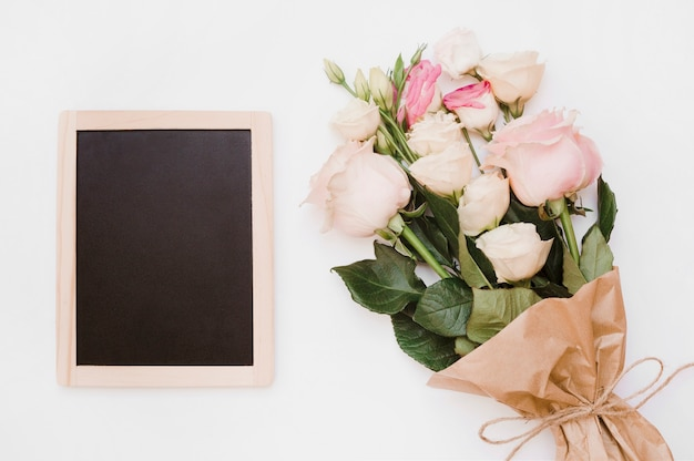 白い背景に花の花束と小さな空白の木製のスレート