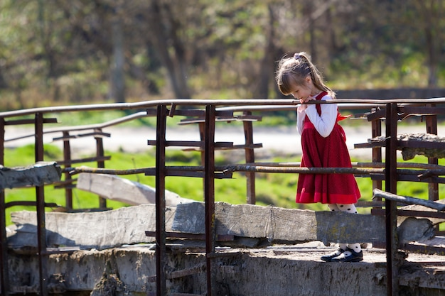 Small blond girl in red dress stands on old cement bridge
