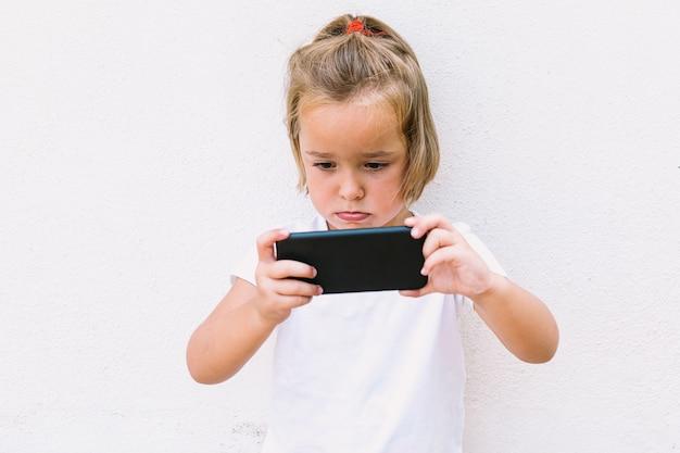 白いtシャツを着て、携帯電話を見て、それを回して、ビデオを見ている小さなブロンドの髪の少女