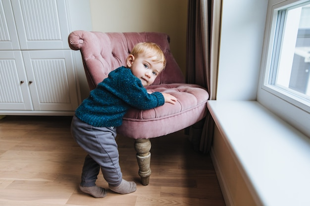 Small blonde child leans at armchair, plays alone at home. little infant teaches to go