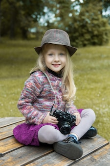 Small blonde girl taking picture using with vintage film camera