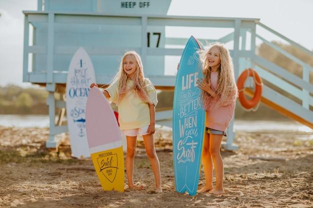 ビーチのライフガードタワーのそばにサーフボードを持つ小さなブロンドの女の子