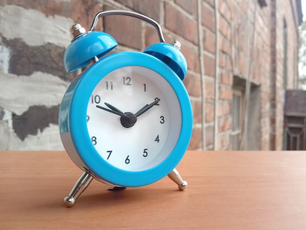 Small blue alarm clock on red building brick wall background in morning sunshine.