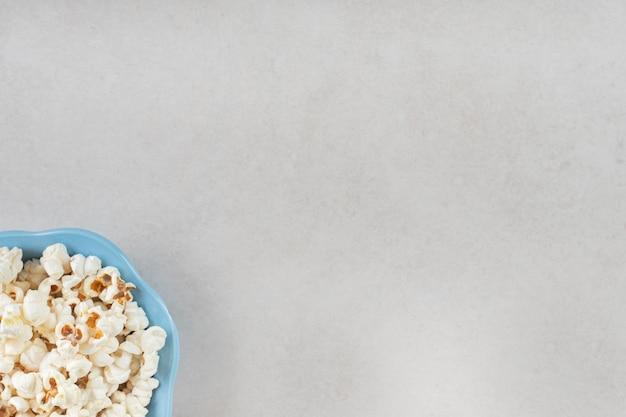 Piccola ciotola blu farcita con croccanti popcorn su un tavolo di marmo.