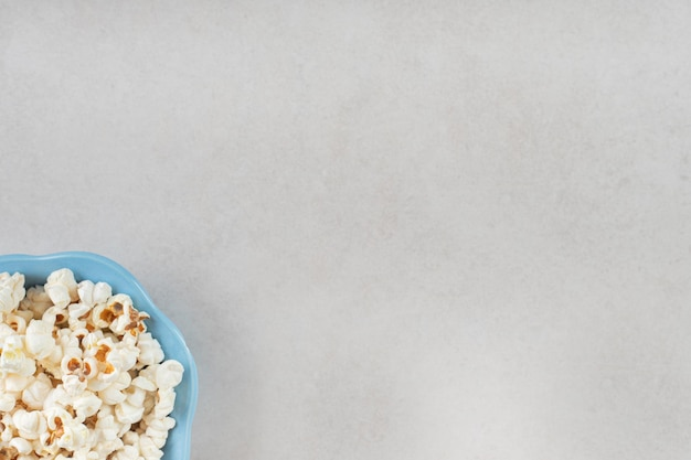 대리석 테이블에 바삭 바삭한 팝콘으로 채워진 작은 파란색 그릇.
