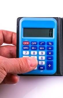 手に小さな青い電卓。