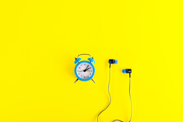 Small blue classic-style alarm clock and blue earphones on bright yellow background.