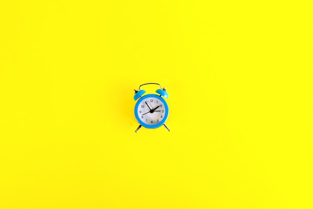 Small blue classic-style alarm clock in minimalist style on bright yellow background.