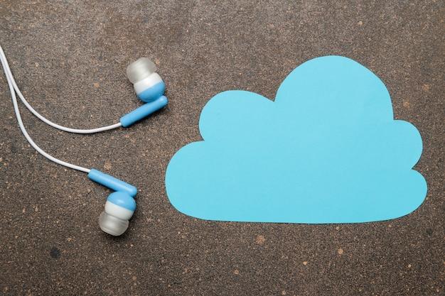 스마트폰용 작은 파란색 헤드폰과 어두운 배경에 파란색 구름. 평면도.