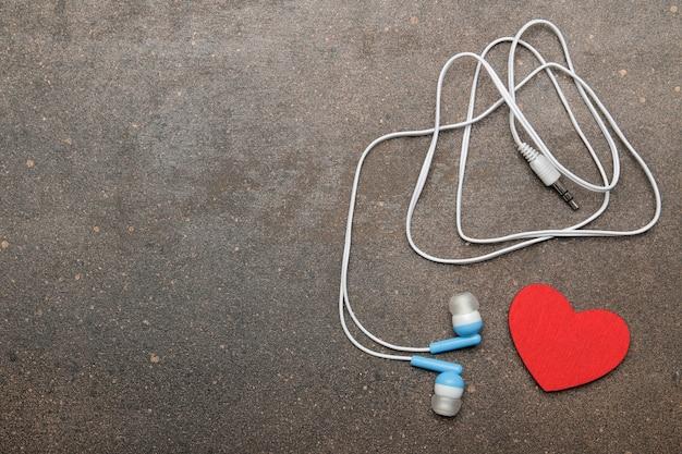 스마트폰용 작은 파란색 헤드폰과 어두운 배경에 장식용 하트. 평면도. 자유 공간
