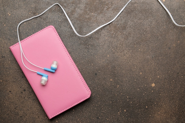 스마트폰용 작은 파란색 헤드폰과 어두운 배경에 분홍색 노트북. 평면도.