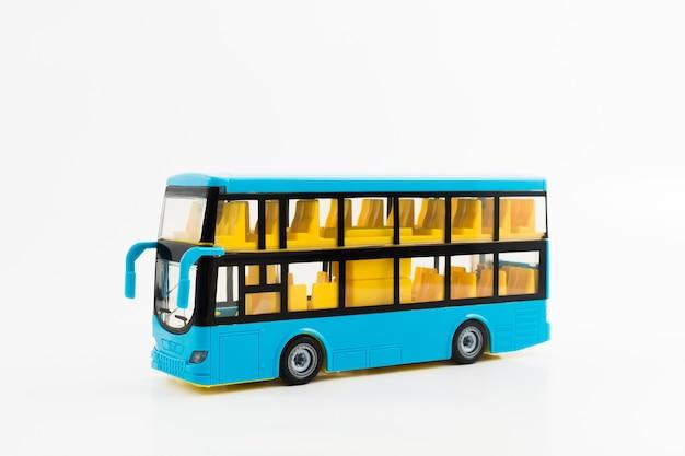 Маленький синий пластиковый туристический двухэтажный автобус с желтыми сиденьями на белом