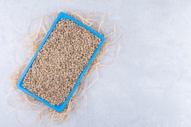 Маленькая синяя тарелка на груде соломы, заполненная коричневой чечевицей на мраморной поверхности