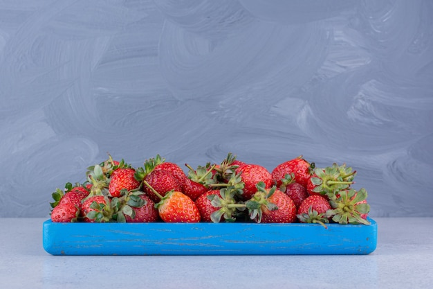 Small blue platter with a portion of strawberries on marble background.