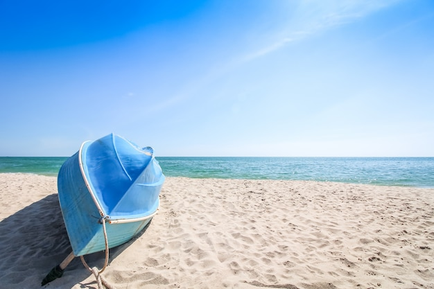 Small blue sailing boat upside down lays on the beach
