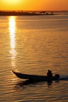 Маленькая лодка на закате плавания по реке