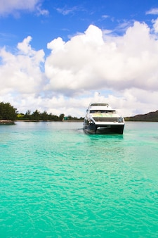 Small boat and cruiser off the coast at tropical island in turquoise water
