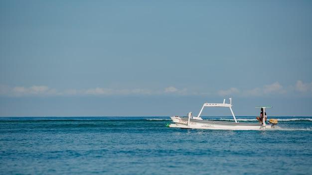 Маленькая лодка плывет по воде с горами.