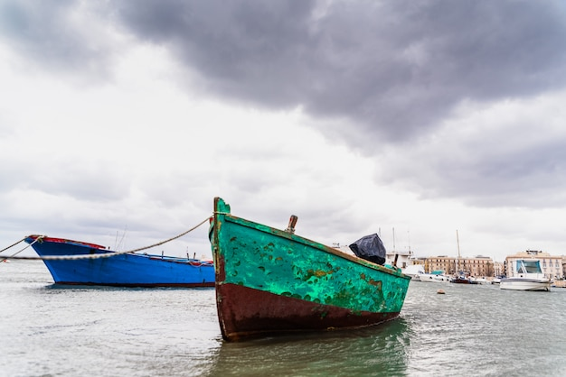 Small boat moored to bari port, italy, during a storm at sea.