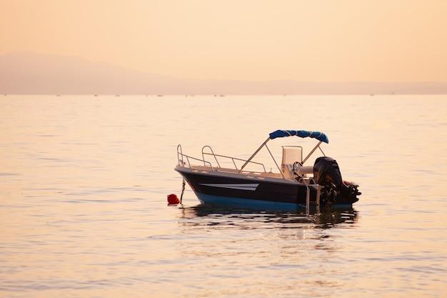 Маленькая лодка в море на закате