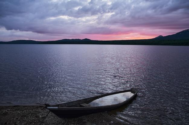 Маленькая лодка затонула в воде ночной закат