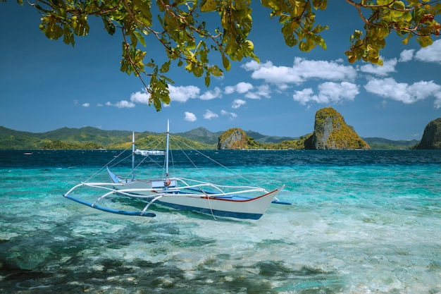 Small boat in turquoise water in blue lagoon. nido, palawan, philippines.