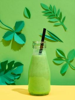 緑のバナナ、パイナップルジュース、ハーブのスムージーの小瓶、緑の紙の葉とカラフルな背景に黒いわら