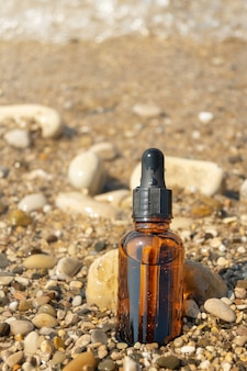 Small bottle with essential oil or serum on sea beach. glass vial with cosmetics for skin care.