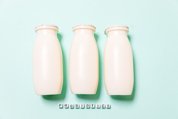 青い背景にプロバイオティクスとプレバイオティクスの乳飲料が入った小瓶