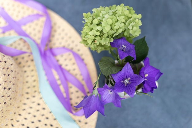 Small bouquet of green hydrangeas and bells next to woman's straw hat ondark blue background. summer vacation concept. image for blog or advertising. selective focus