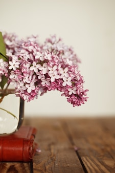 Small bouquet of lilac in glass vase as detail of interior, on wood background