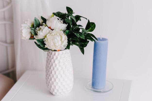 Небольшой букет из живых цветов, белых пионов и зелени в вазе и свече. свадебные цветы, букет невесты крупным планом. домашний декор на деревянной тумбочке, винтажном стиле. предметы украшения.