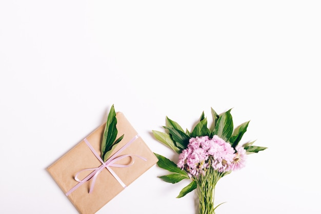 Small bouquet of pink carnations and a gift with ribbon on white background