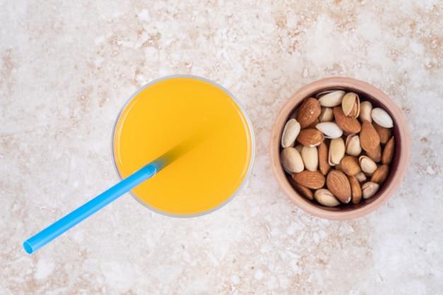 Una piccola ciotola di mandorle e pistacchi e un bicchiere di succo