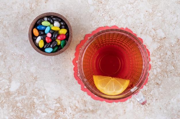 Una piccola ciotola di caramelle assortite e una tazza di tè