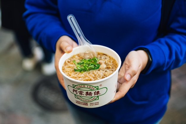 Small bowl of ay-chung flour-rice noodle with pig intestines, and cilantro in a steaming hot broth.