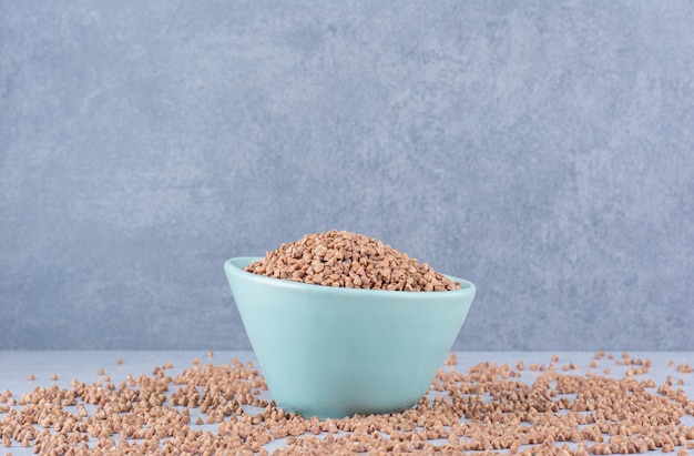 Small bowl of buckwheat placed in the middle of scattered grains on marble surface