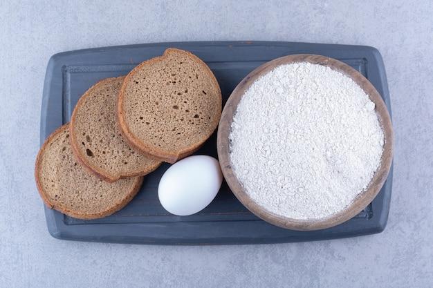 Una piccola ciotola di farina, un uovo e tre fette di pane su un bordo blu marino su una superficie di marmo