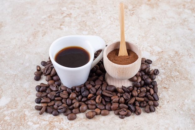 A small bowl of ground coffee powder and a cup of coffee sitting on a pile of coffee beans