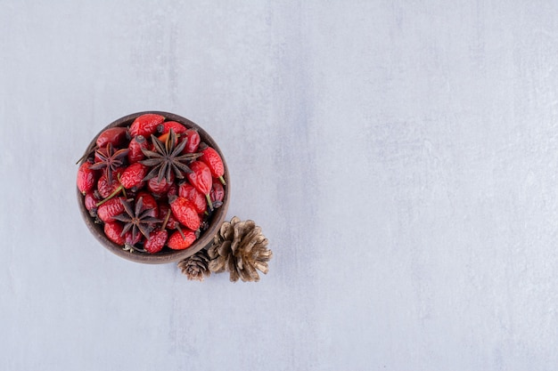 Small bowl of hips and anise next to pine cones on white background.