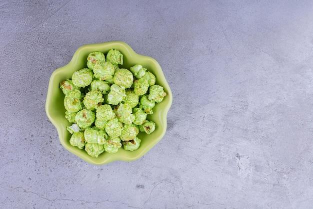 Piccola ciotola contenente un modesto mucchio di popcorn ricoperti di caramelle su sfondo marmo. foto di alta qualità