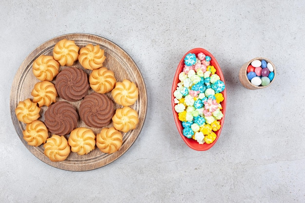 작은 사탕 그릇, 팝콘 사탕 큰 그릇 및 대리석 배경에 맛있는 쿠키 트레이. 고품질 사진