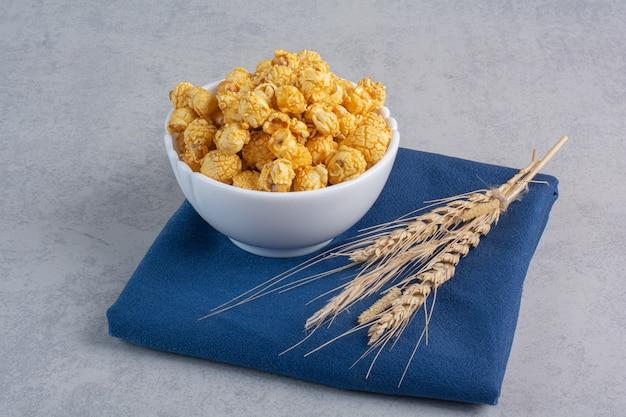 大理石にキャンディーでコーティングされたポップコーンと小麦の茎の小さなボウル。