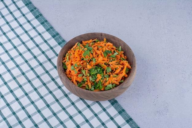 대리석 바탕에 식탁보에 당근 샐러드의 작은 그릇. 고품질 사진