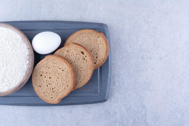 大理石の表面の海軍の板に小麦粉、卵、3つのパンのスライスの小さなボウル